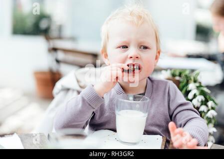 Girl eating chocolate cookie - Stock Image