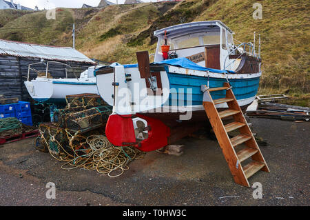 An old fishing boat and lobster / crab creel in the harbor of Portknockie, Scotland, UK. - Stock Image