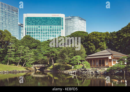 A traditional tea house in Hamarikyu Gardens Tokyo nessled amongst the modern hotels and offices - Stock Image