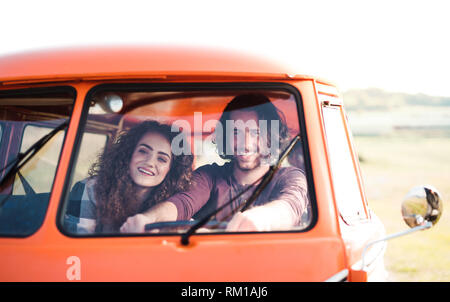 A young couple on a roadtrip through countryside, driving minivan. - Stock Image