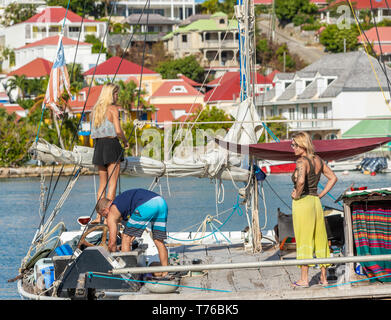 Two women and one man setting up a catamaran in the port of Gustavia, St Barts - Stock Image