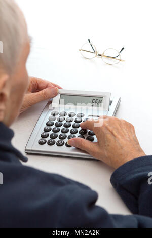 Very old woman with decreasing vision sitting at a table using a desktop calculator with a large keypad - Stock Image