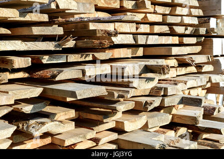 Roughly cut piles of timber planks for home and design construction in sunlight - Stock Image