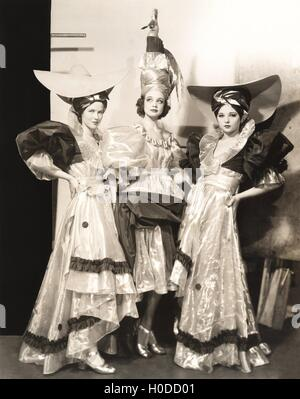 Three dancers in long dresses and large hats - Stock Image