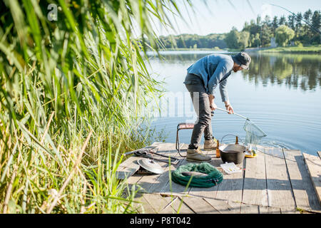 Fisherman catching fish with fishing net standing on the pier near the lake in the morning - Stock Image