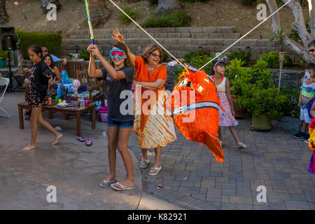 girl, hitting a pinata, pinata filled with candy sweets and toys, birthday party, Castro Valley, Alameda County, California, United States - Stock Image