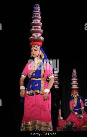 Indian woman wearing traditional dress and  dance with pots on the head - Stock Image