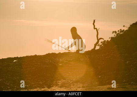 Boy with stick at sunset Boy with stick at sunset dusk late evening silhouette - Stock Image