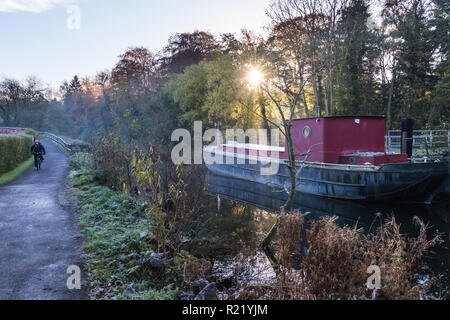 Sunlight bursts through the trees and mist on a cold frosty morning behind a canal barge with path alongside with cyclist. Lagan Towpath, Belfast, N.I - Stock Image