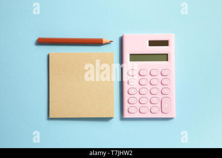 Pink digital calculator and memo note pad and brown colored pencil on blue background - Stock Image