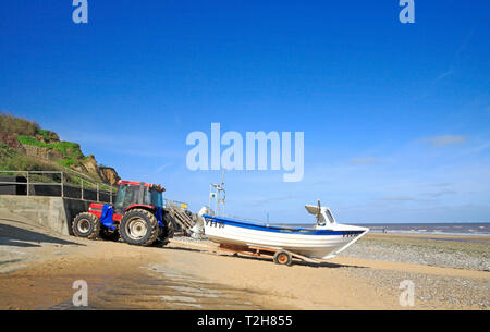 A fishing boat and tractor by the seawall on the North Norfolk beach at East Runton, Norfolk, England, United Kingdom, Europe. - Stock Image