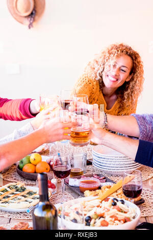 Friend at home or restaurant enjoying and celebrating together clinking and toasting with beers - table full of food and cheerful happy people having  - Stock Image