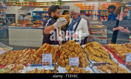 LONDON ENGLAND BRICK LANE INDIAN FOOD SHOP WINDOW WITH CUSTOMERS BUYING VEGETABLE SAMOSAS CHICKEN TIKKA AND CHANNA ROLLS - Stock Image