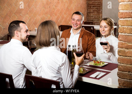 Glad company of friends eating delicious lunch in country club - Stock Image