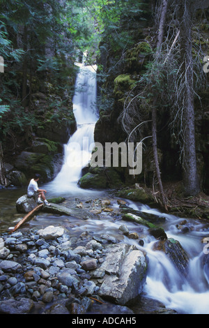 A hiker in sits on a rock along Little North Fork Falls in Kootenai National Forest, Montana, United States of America - Stock Image