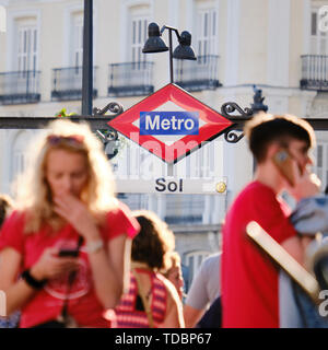 People using mobile phones near metro station of Sol in Madrid Spain - Stock Image