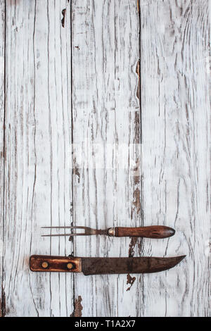 Vintage meat fork and butcher's knife over top a white rustic wood table / background. Image shot from overhead view. - Stock Image