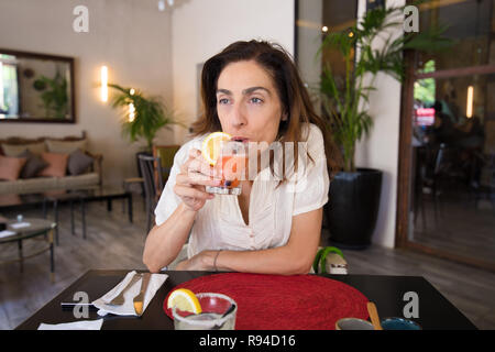adult woman with white shirt drinking from straws strawberry margarita with slice lemon  of glass in hand, sitting in black table with red mat straw o - Stock Image