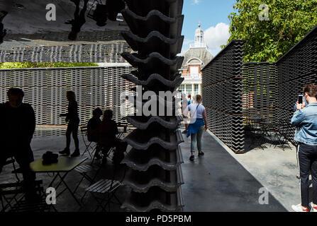 Inside pavilion looking to Serpentine Gallery with people. Serpentine Summer Pavilion 2018, London, United Kingdom. Architect: Frida Escobedo, 2018. - Stock Image
