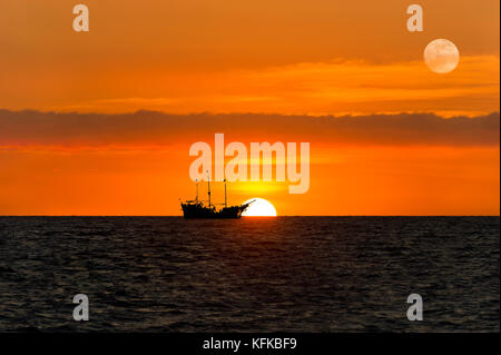 Ship pirate silhouette is a pirate ship sitting at sea watching the ocean sunset as the moon rises in the sky. - Stock Image