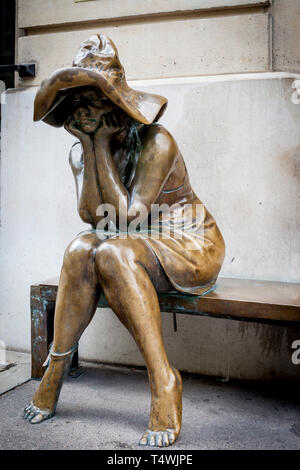 Bronze statue of seated peasant girl outside the Hungarian Institute, Paris France - Stock Image