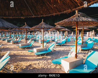 Chairs and umbrellas at Porto Vathy Marble Beach in Thasos, Greece - Stock Image