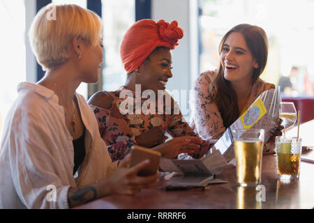 Happy young women friends looking at map, drinking cocktails in bar - Stock Image
