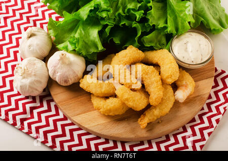 Fried organic coconut shrimp in breading with cocktail sauce and salad - Stock Image
