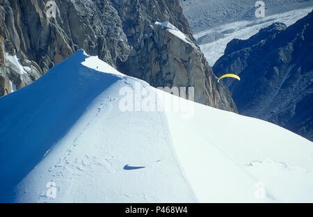 A parapente casts its shadow as it takes off from a mountain in the French Alps - Stock Image