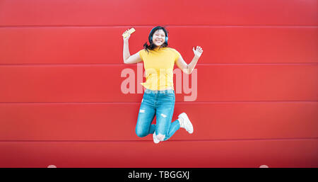 Happy Asian girl jumping while listening music outdoor - Crazy Chinese woman having fun dancing a song against red background - Stock Image