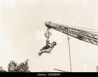 Two people dangling from crane - Stock Image