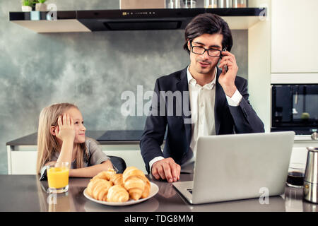 Happy little girl watching his father that works - Stock Image