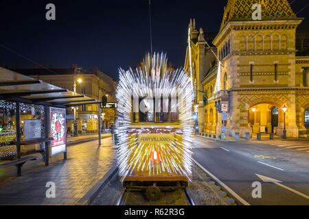 Budapest, Hungary - Festively decorated light tram (Fenyvillamos) on the move at Fovam Square with the Great Market Hall (Vasarcsarnok) by night. Chri - Stock Image