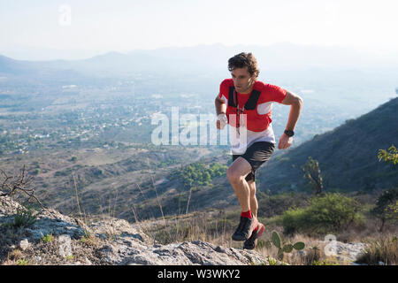 A strong, athletic middle aged male trail runner explores the rocky, arid trails of the mountains surrounding the town of El Arenal, Hidalgo, Mexico. - Stock Image