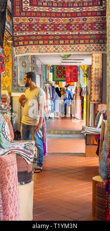 Man standing in portico lined with traditional rugs and fabrics on display in Arab Street Kampong Glam Singapore - Stock Image