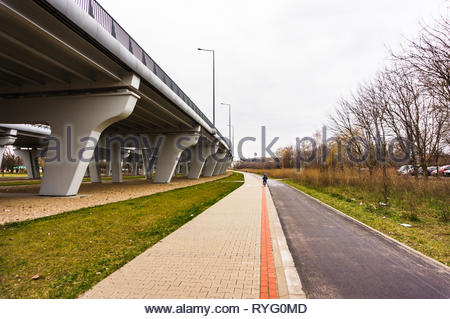 Poznan, Poland - March 3, 2019: Bicycle route and pathway with red line next to a bridge in a park. - Stock Image