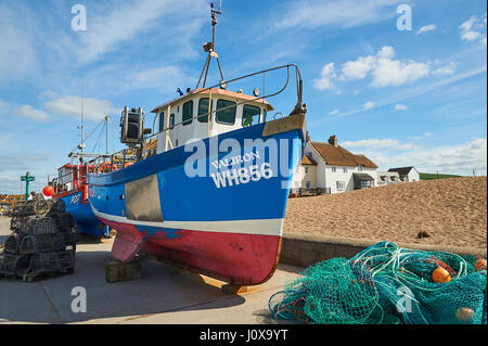 Colourful fishing boats left on the quayside in the Dorset seaside town of West Bay. - Stock Image