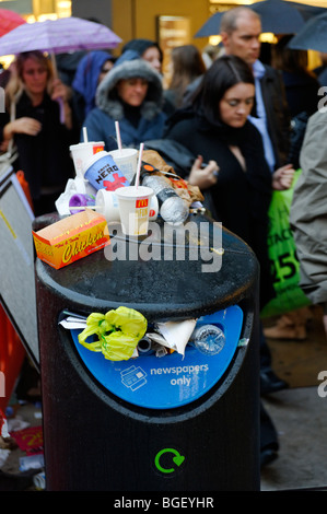 Overflowing public newspaper recycling bin with mixed waste. London. Britain. UK - Stock Image