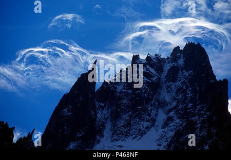 Alpine peaks silhouetted against high altitude clouds - Stock Image