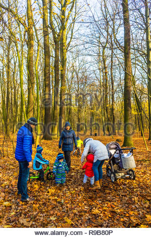Poznan, Poland - November 17, 2018: Parents with their children standing on fallen leaves between trees at the Debinski forest.  - Stock Image