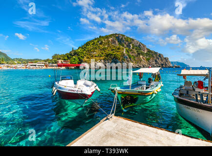 Boats docked in the crystal turquoise waters near the shore of the sandy Palaiokastritsa beach and bay on the Aegean island of Corfu, Greece. - Stock Image