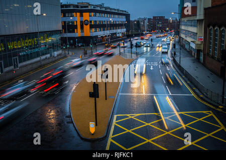 Traffic moving along wet city roads as night falls. - Stock Image