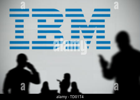 The IBM logo is seen on an LED screen in the background while a silhouetted person uses a smartphone in the foreground (Editorial use only) - Stock Image