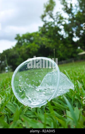 Discarded single use plastic cup in laying in grasse. - Stock Image