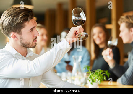 Young man with wine glass at a wine tasting proves quality of red wine - Stock Image