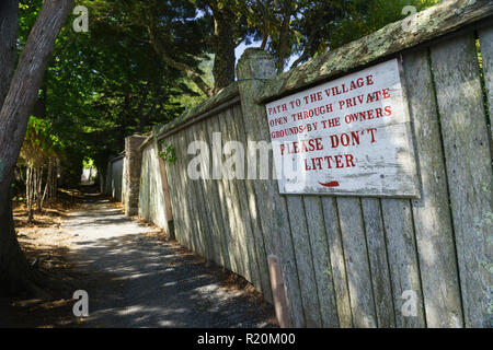 Path opened through private grounds and no littering sign on an old wooden fence, Bar Harbor, Maine, USA. - Stock Image