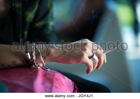 Hand with cigarette and bracelets and tatoo - Stock Image