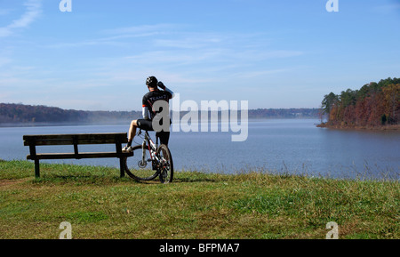 Cyclist (silhouette) watching fog lift from a lake while taking on a cell phone - Stock Image
