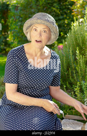 Senior white woman in a blue polka dotted and straw hat in her garden yard showing an exaggerated surprise, joy - Stock Image