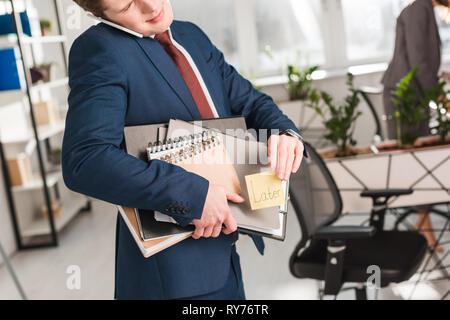 cropped view of businessman holding folders and sticky note with later lettering and talking on smartphone in office - Stock Image